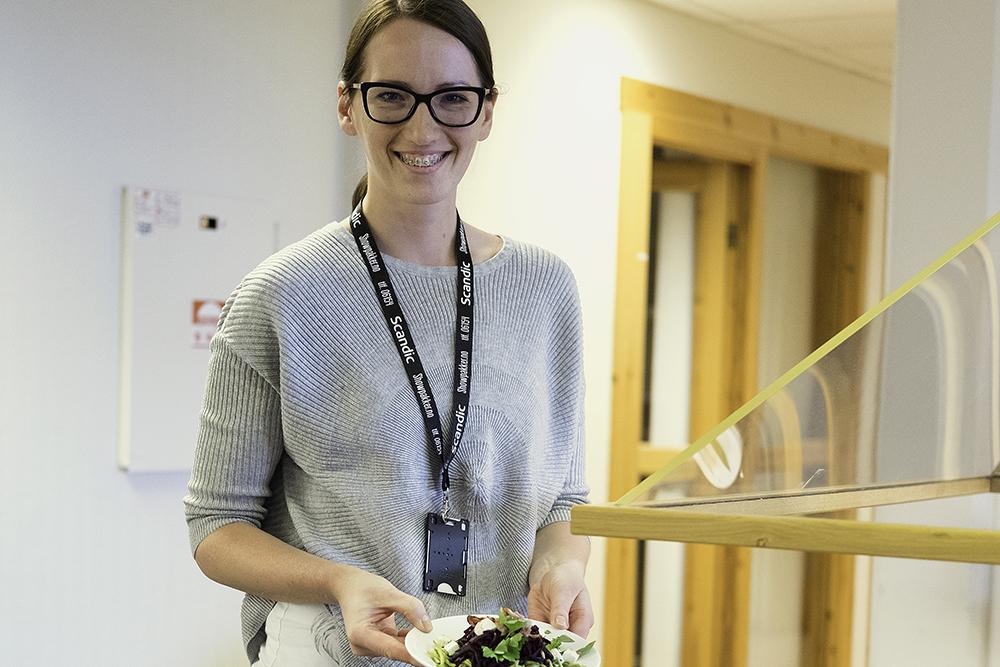 Ung glad dame med en skål med salat ved lunsjdisken på Kompetansesenteret
