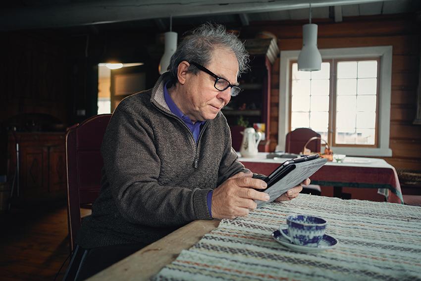 Bilde av Jo Øvergård som sitter med nettbrett ved kjøkkenbordet.