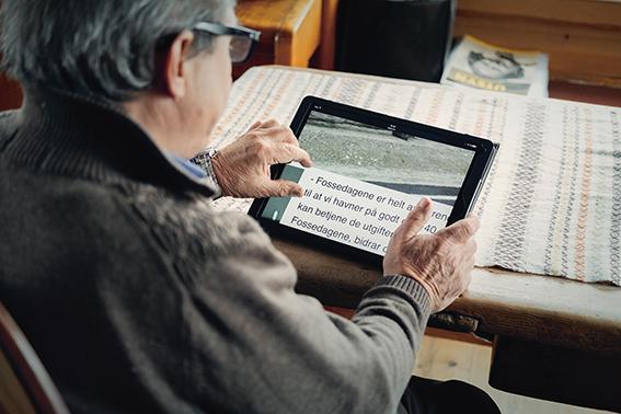 Bilde av Jo Øvergård som leser NØKs nettsider på nettbrett.